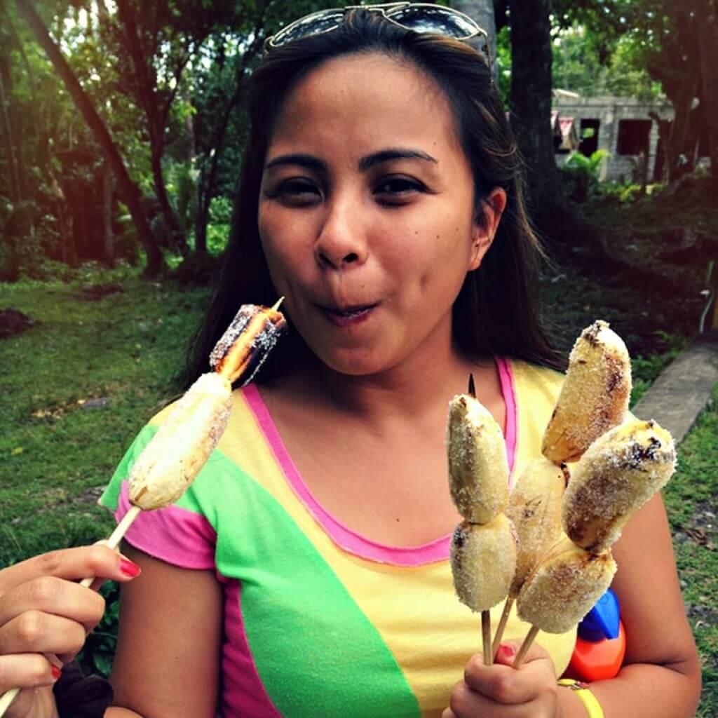 "alt=""Filipina Eating Popular Pinoy Snack called Ginanggang"""