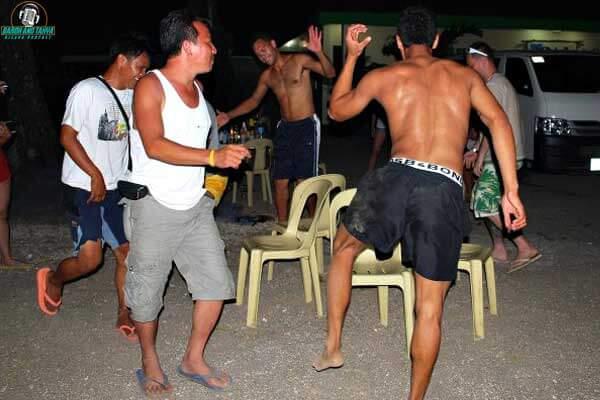 "alt=""Filipino men are happy dancing around the chairs"""