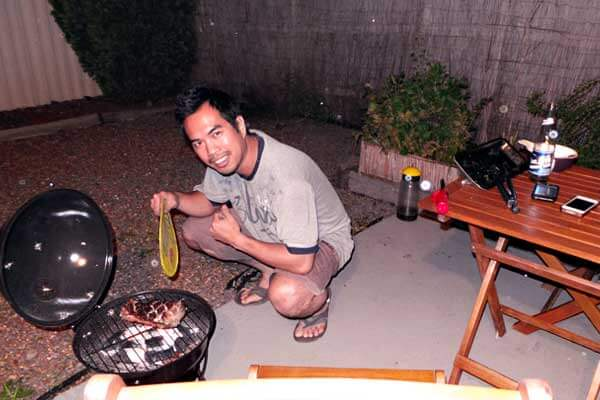"alt=""A Filipino is grilling a slice of meat for dinner"""