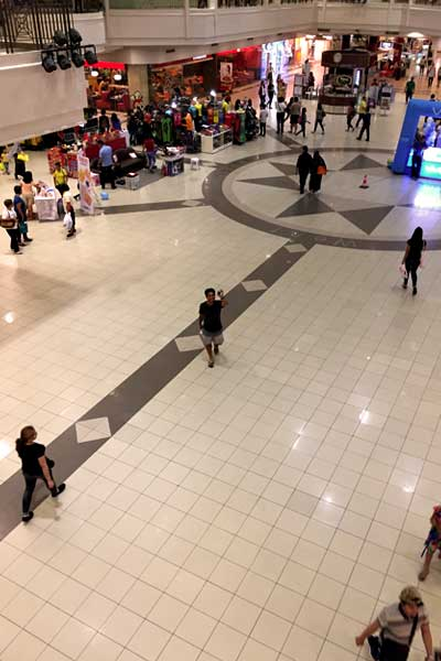 """alt=""""Filipino man walking on the mall with the crowd"""""""