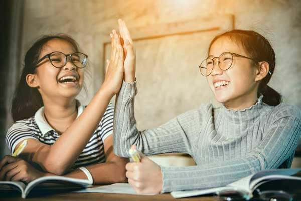 "alt=""Two Filipina students look so happy in the classroom"""
