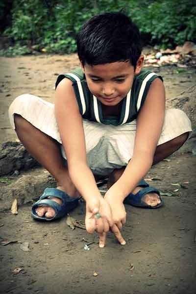 "alt=""Filipino childhood memories a boy is playing a marble game"""