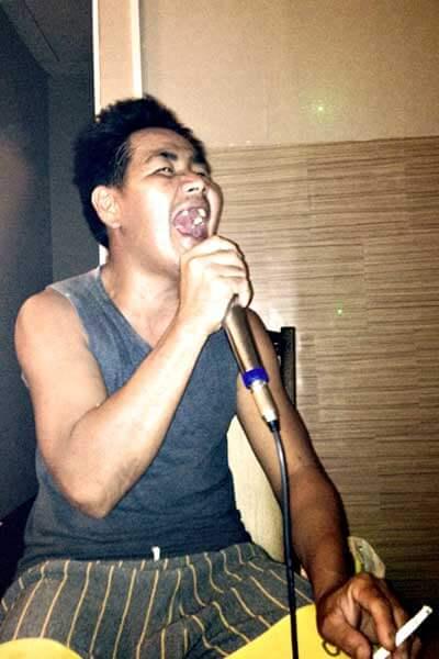 "alt=""Filipino man happily singing in the karaoke bar"""