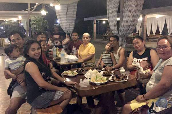 "alt=""Filipino families are happily eating their dinner at the park"""