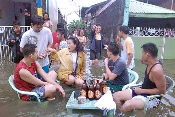 "alt=""Resilient in Filipino drinking session in the flood"""