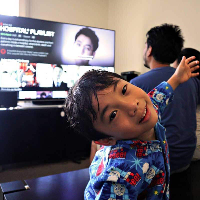 "alt=""A Boy is smiling while parents watching tv"""