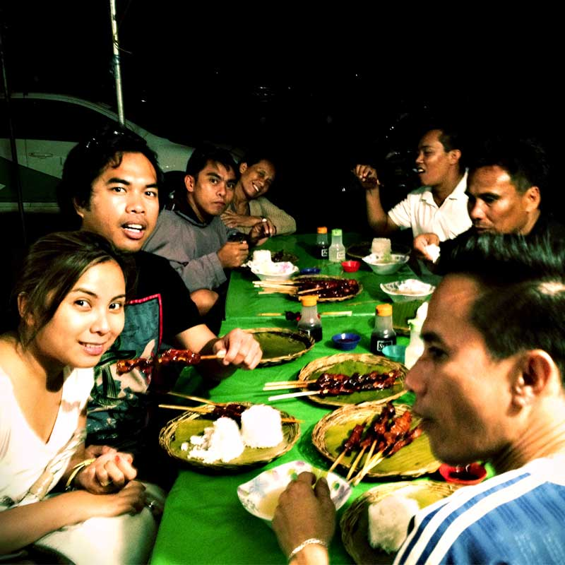 """alt=""""A happy family gather around to eat barbeque"""""""
